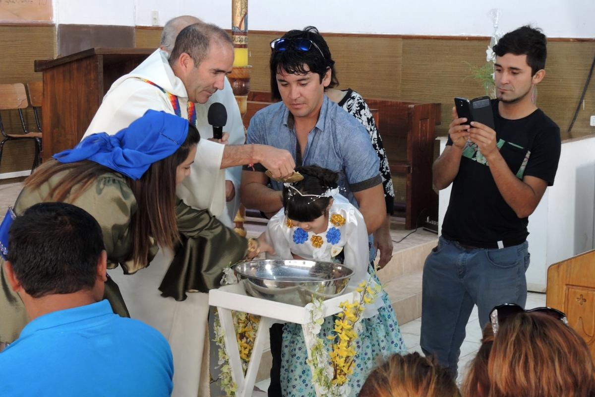A young girl is baptized at La Tirana. Many families defer sacraments so that these can be celebrated during the feast.