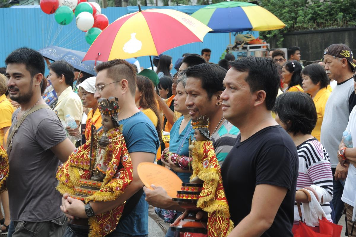 Filipino men carry images of Santo Niño in a procession during the feast in Cebu.