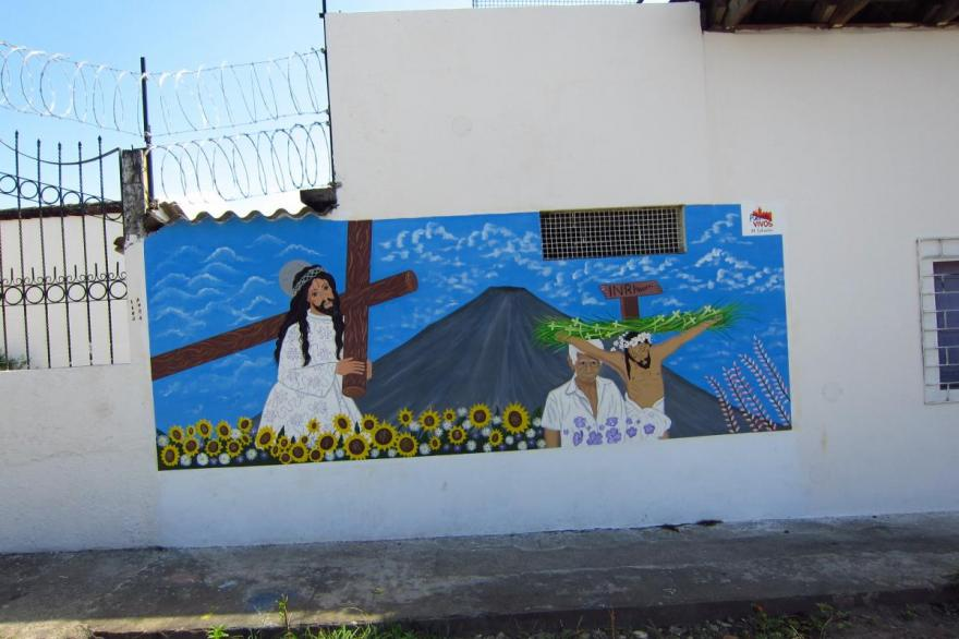 Just outside the Hermandad de Jesús Nazareno de Niños, this mural uses the towering volcano above the town to locate the festivities, and an image of the Nazareno statue that is featured in their Holy Week processions. Izalco, El Salvador.