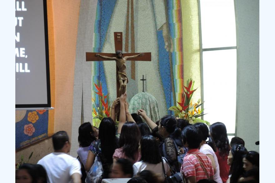 Filipino Catholics reaching to touch the feet of the Crucifix as they exit Mass. St. Joseph Church, Hong Kong.